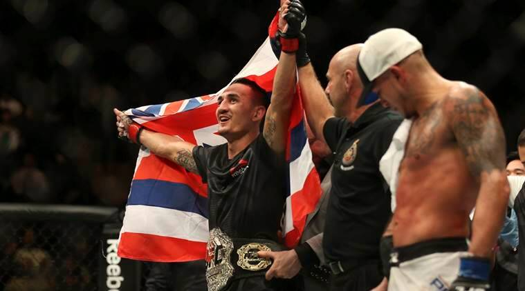 Max Holloway celebrates after defeating Anthony Pettis, right, to win the interim featherweight title during the main event of a mixed martial arts bout at UFC 206, Saturday, Dec. 10, 2016, at the Air Canada Centre in Toronto. (Peter Power/The Canadian Press via AP)