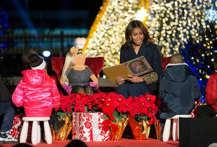 FILE - In this Dec. 3, 2015, file photo, first lady Michelle Obama with Miss Piggy, left, read 'Twas the Night Before Christmas for children on stage during the National Christmas Tree Lighting ceremony at the Ellipse in Washington. When Michelle Obama considered the daunting prospect of becoming first lady, she purposely avoided turning to books by her predecessors for guidance. Instead, she turned inward. (AP Photo/Pablo Martinez Monsivais)