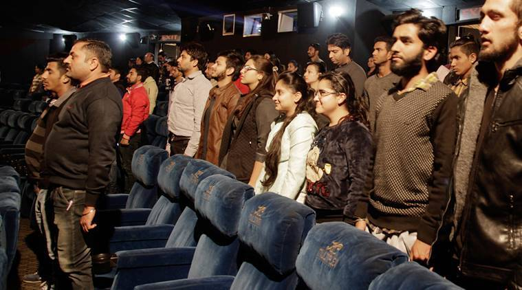 Indian movie goers stand up as national anthem is played at a movie hall before the screening of a movie in Jammu, India, Tuesday, Dec. 13, 2016. A ruling by India's Supreme Court last month said that the anthem must be played before every film screening in the country and that audiences must stand. The court said the rule was aimed at instilling a sense of patriotism. (AP Photo/Channi Anand)