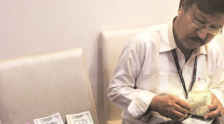 A bank official counting notes seized by the DGCEI after raids on a prominent Pune firm. Express