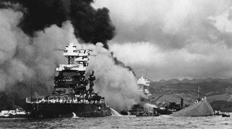 FILE - In this Dec. 7, 1941 file photo, part of the hull of the capsized USS Oklahoma is seen at right as the battleship USS West Virginia, center, begins to sink after suffering heavy damage, while the USS Maryland, left, is still afloat in Pearl Harbor, Oahu, Hawaii. (AP Photo/U.S. Navy, File)