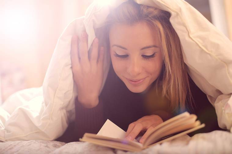 A young beautiful girl lying in her bed and reads a book calmly and positively