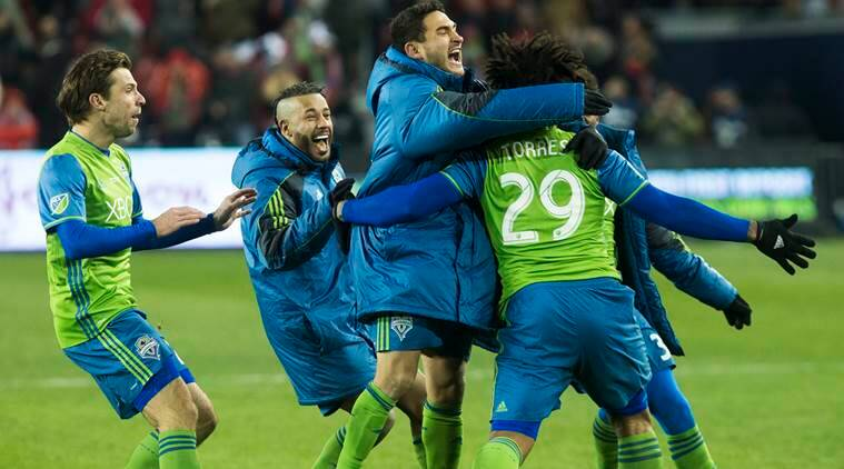 Seattle Sounders midfielder Cristian Roldan, center, along with teammates chase down Seattle Sounders defender Roman Torres (29) after he scored the game-winning shootout goal to defeat Toronto FC in an MLS Cup final soccer game in Toronto, Saturday, Dec. 10, 2016. (Chris Young/The Canadian Press via AP)