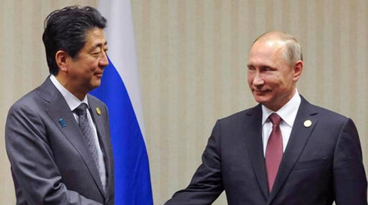 FILE - In this Nov. 20, 2016, file photo, Japanese Prime Minister Shinzo Abe, left, shakes hands with Russian President Vladimir Putin during their meeting at the Asia-Pacific Economic Cooperation (APEC) forum in Lima, Peru. Abe will welcome Putin at a hot springs resort in in western Japan on Thursday, Dec. 15, 2016. Despite the cozy setting, they face tough negotiations over a 70-year-old island dispute that has kept them from signing a peace treaty. (Mikhail Klimentyev/Sputnik, Kremlin Pool Photo via AP, File)