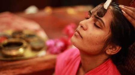 Therapist treating applying face pack to a young woman in an ayurvedic spa.