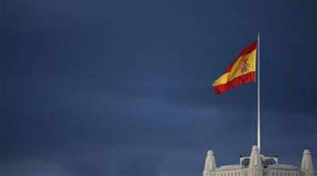 A Spanish flag flutters in the wind on the top of Madrid's city hall as rain clouds appear in the background