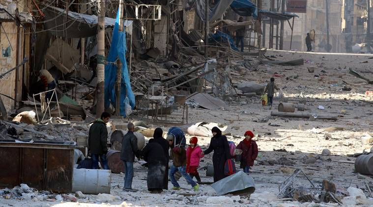 Syrians walk over rubble of damaged buildings, while carrying their belongings, as they flee clashes between government forces and rebels in Tariq al-Bab and al-Sakhour neighborhoods of eastern Aleppo towards other rebel held besieged areas of Aleppo, Syria November 28, 2016. Reuters.