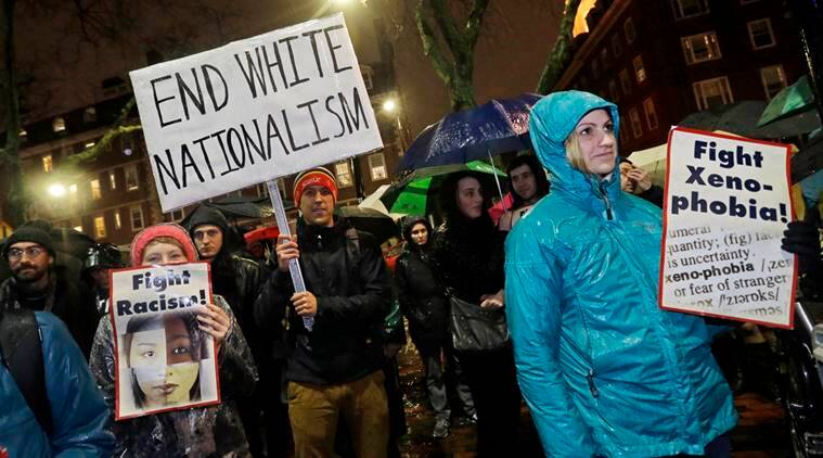 Protesters hold signs outside Harvard's John F. Kennedy School of Government, Wednesday, Nov. 30, 2016, in Cambridge, Mass. where the Institute of Politics is hosting a forum featuring political strategists from the 2016 presidential election campaigns. President-elect Donald Trump advisor, Stephen K. Bannon, was on the list of those scheduled to attend, but reportedly changed his plans. (AP Photo/Elise Amendola)