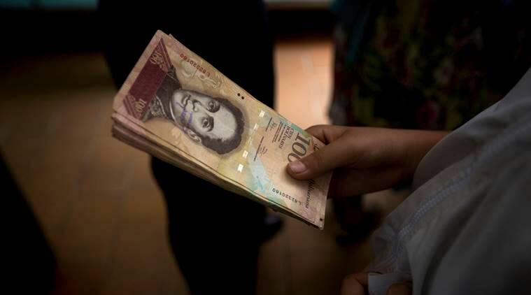 "A customer holds a stack of 100-bolivar notes at a bakery in downtown Caracas, Venezuela, Monday, Dec. 12, 2016. Venezuelans are rushing to spend their 100-bolivar notes after a surprise announcement that they will be taken out of circulation this week. President Nicolas Maduro said on Sunday that his government would be pulling the bills to stop the ""mafias"" who smuggle contraband on the Colombian border. (AP/Photo/Fernando Llano)"