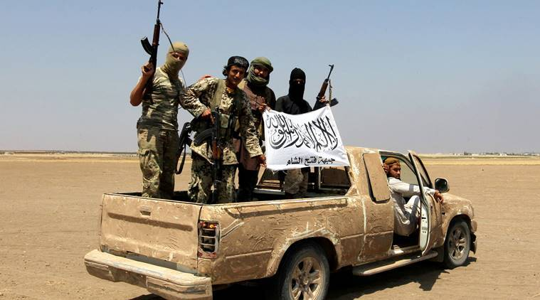 FILE PHOTO: Fighters of the Syrian Islamist rebel group Jabhat Fateh al-Sham cheer on a pickup truck after a Russian helicopter was shot down in the north of Syria's rebel-held Idlib province, Syria, August 1, 2016. REUTERS/Ammar Abdullah/File Photo