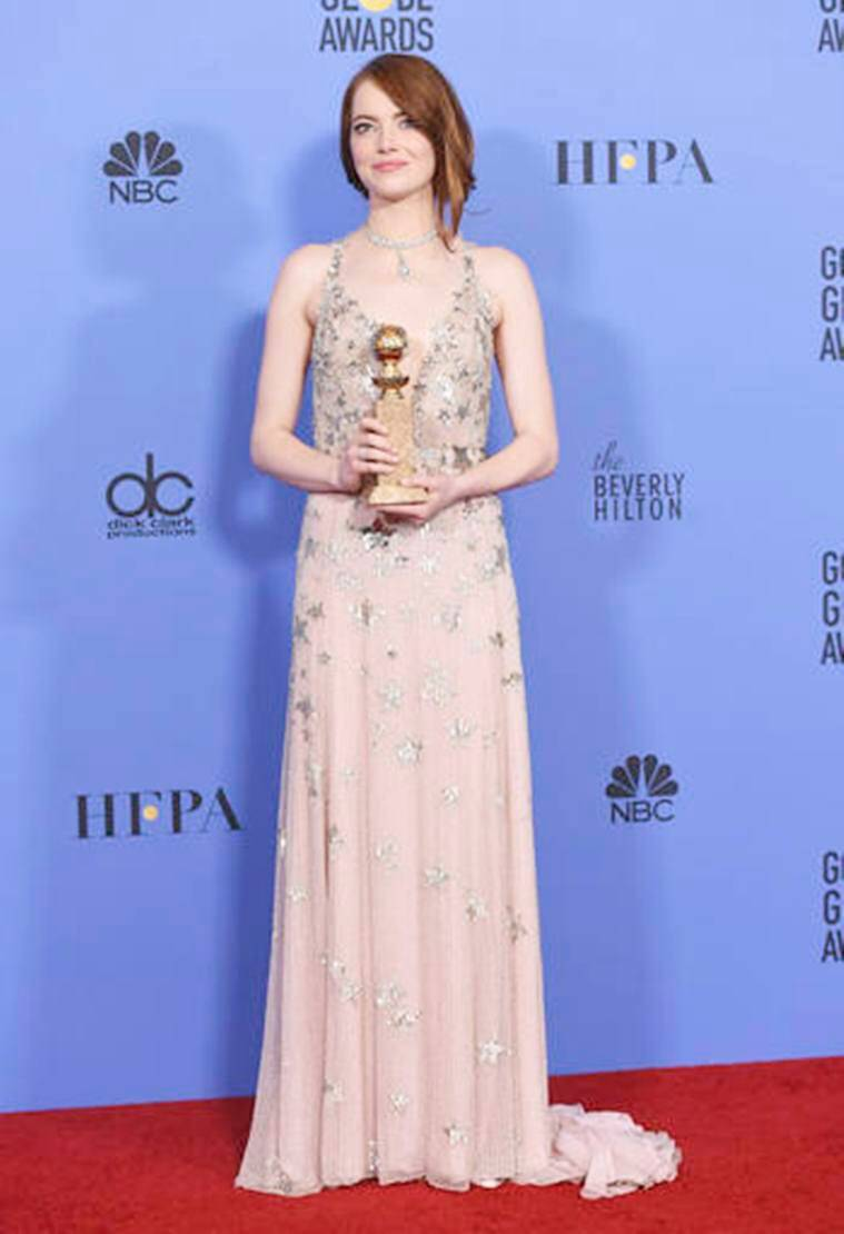 """Emma Stone poses in the press room with the award for best performance by an actress in a motion picture - musical or comedy for """"La La Land"""" at the 74th annual Golden Globe Awards at the Beverly Hilton Hotel on Sunday, Jan. 8, 2017, in Beverly Hills, Calif. (Photo by Jordan Strauss/Invision/AP)"""