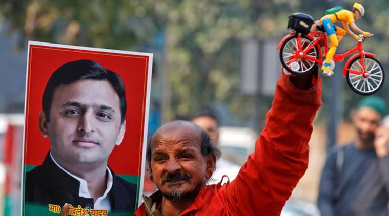 A Samajwadi (SP) party worker holds a toy bicycle representing the party's symbol and a poster of chief minister of northern state of Uttar Pradesh Akhilesh Yadav, following the Election Commission's decision to allot the bicycle symbol in Akhilesh's favour, outside the party's headquarters in Lucknow, India, January 17, 2017. REUTERS/Pawan Kumar