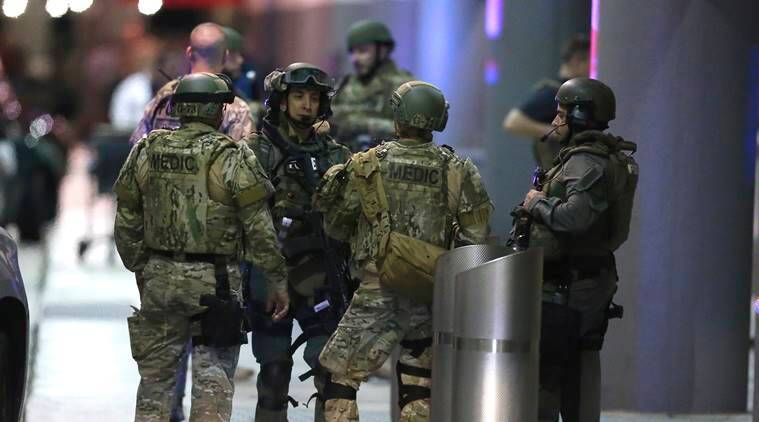 Police waiting to escort employees and passengers walking outside terminal 2 at the scene of a deadly shooting at Fort Lauderdale–Hollywood International Airport, Friday, January 6, 2017, in Fort Lauderdale, Fla. An Army veteran who complained that the government was controlling his mind drew a gun from his checked luggage on arrival at the Fort Lauderdale airport and opened fire in the baggage claim area Friday, killing several people and wounding others, authorities said. (David Santiago/El Nuevo Herald via AP)