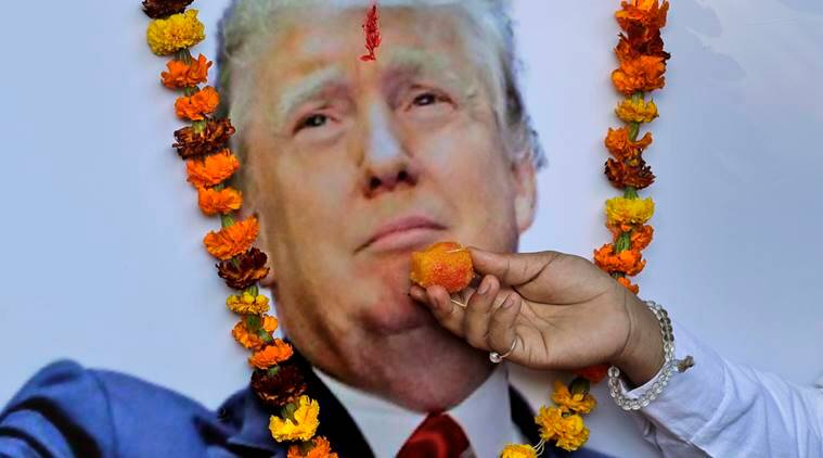 About a dozen activists of Hindu Sena, a local right wing group, garland and offer sweets to a photograph of U.S President-elect Donald Trump as they celebrate ahead of his inauguration at Jantar Mantar, a popular place for protest gatherings in New Delhi, India, Thursday, Jan.19, 2017. (AP Photo/Manish Swarup)