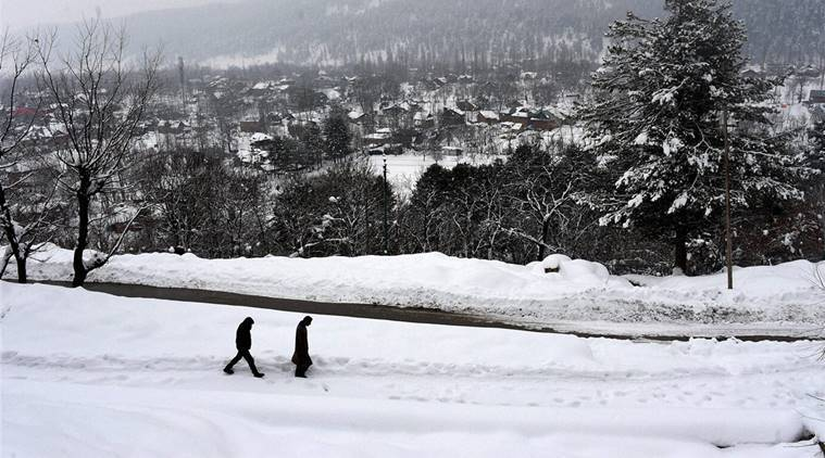 Tangmarg (Kashmir): Two youth walking over snow to reach their destination near Tangmarg along Srinagar-Gulmarg road in north Kashmir on Wednesday. High altitude areas of Kashmir experienced heavy snowfall over the past three days, attracting a large number of tourists. PTI Photo by S Irfan    (PTI1_18_2017_000197B)