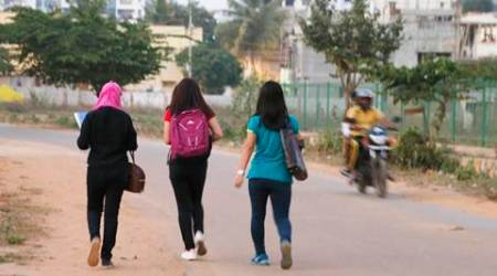 A motorist rides past young Indian girls in Bangalore, India, Wednesday, Jan. 4, 2017. Police detained at least six suspects Wednesday, days after outrage erupted in India over several women being groped and molested during New Year's Eve celebrations in the southern city of Bangalore, the country's information technology hub. The incident highlights the persistent violence against women in India despite tougher laws against sexual assault imposed after the December 2012 death of a young woman who was gang-raped on a bus in New Delhi. (AP Photo/Aijaz Rahi)
