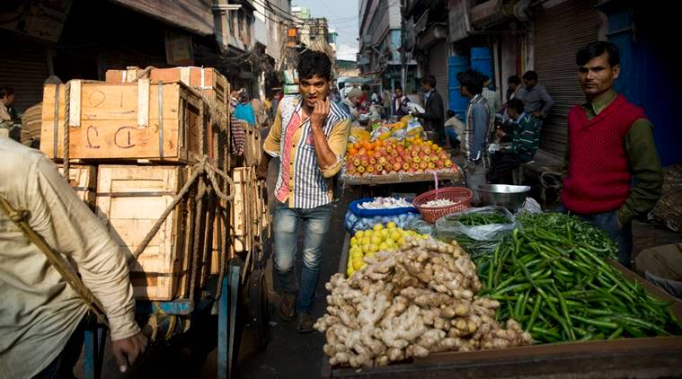 Indian vegetable vendors, right, await customers as laborers transport goods on a cart, left, in New Delhi, India, Tuesday, Jan. 31, 2017. India's federal budget is scheduled to be presented in Parliament Wednesday. (AP Photo/Tsering Topgyal)