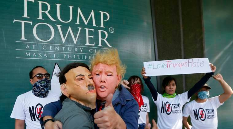"Protesters, one wearing a Donald Trump mask and another with an Adolf Hitler mask, embrace as others display a #lovetrumpshate hashtag during a brief picket at the Trump Tower hours after Trump was sworn in as the 45th President of the United States Saturday, Jan. 21, 2017 in the financial district of Makati city east Manila, Philippines. Pledging emphatically to empower America's ""forgotten men and women,"" Donald Trump was sworn in as President of the United States on Friday, taking command of a riven nation facing an unpredictable era under his assertive but untested leadership. (AP Photo/Bullit Marquez)"