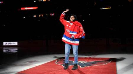 Fatima Al Ali, of the UAE, waves to the crowd before she took part in a ceremonial puck drop before an NHL hockey game between the Washington Capitals and the Detroit Red Wings in Washington