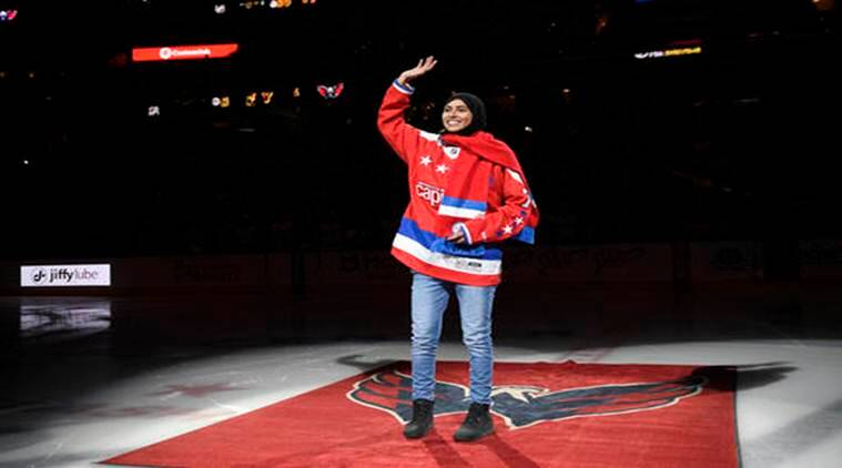 Fatima Al Ali, of the United Arab Emirates, waves to the crowd before she took part in a ceremonial puck drop before an NHL hockey game between the Washington Capitals and the Detroit Red Wings in Washington. (Source:AP)
