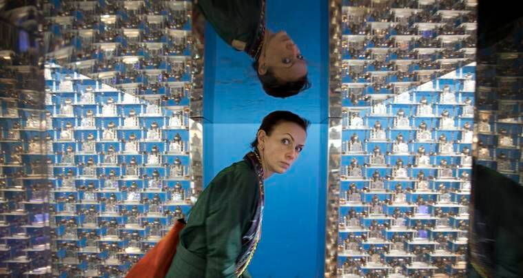 A woman looks inside an art installation titled Taj by Sudarshan Shetty during the India Art Fair in New Delhi, India, Thursday, Feb. 2, 2017. The four day art fair brings together a number of modern and contemporary artists to present their works. (AP Photo/Tsering Topgyal)