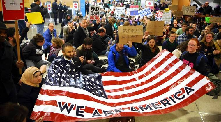 """Demonstrators sit down in the concourse and hold a sign that reads """"We are America,"""" as more than 1,000 people gather at Seattle-Tacoma International Airport, to protest President Donald Trump's order that restricts immigration to the U.S., Saturday, Jan. 28, 2017, in Seattle. President Trump signed an executive order Friday that bans legal U.S. residents and visa-holders from seven Muslim-majority nations from entering the U.S. for 90 days and puts an indefinite hold on a program resettling Syrian refugees. (Genna Martin/seattlepi.com via AP)"""