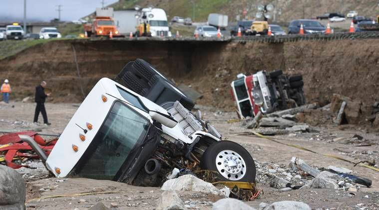 Officials look over the scene, Saturday, Feb. 18, 2017, where a tractor trailer fell Friday from southbound Interstate 15 where part of the freeway collapsed due to heavy rain in the Cajon Pass, Calif., Saturday, Feb. 18, 2017 A huge Pacific storm that parked itself over Southern California and unloaded, ravaging roads, opening sinkholes eased off Saturday but it was only a temporary reprieve as new storms took aim farther north. (David Pardo/The Daily Press via AP)