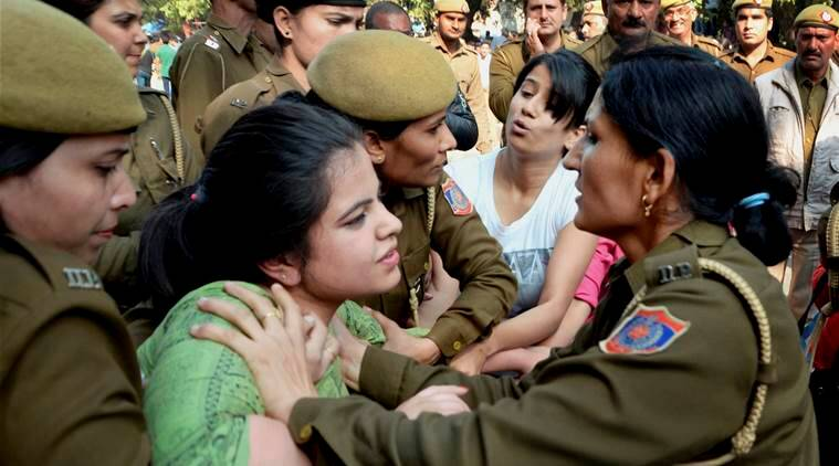 Police detain ABVP activists after their clash with AISA students at Delhi University in Delhi on Wednesday. PTI Photo