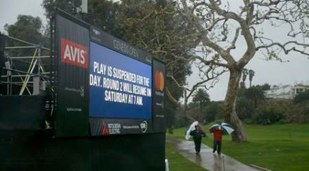 Spectators walk to the clubhouse after play was suspended during the second round of the Genesis Open golf tournament at Riviera Country  (Source: AP)
