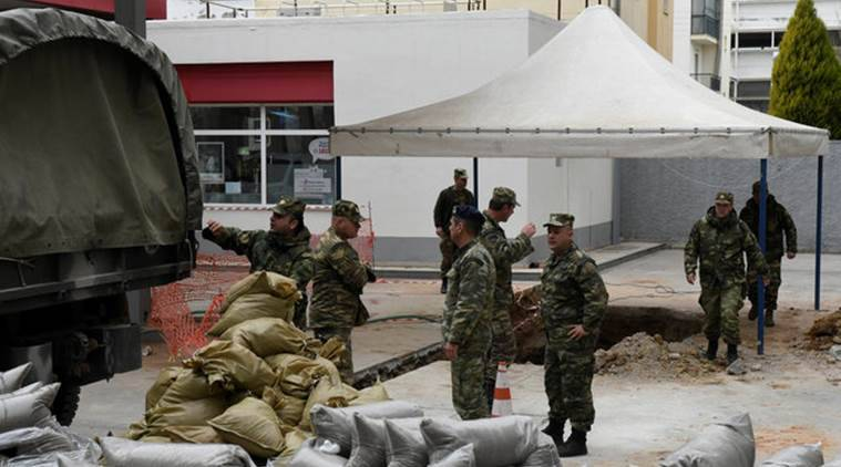 Military officers unload sacks of sand next to a hole in the ground (R), where a 250 kg World War Two bomb was found during excavation works at a gas station, before an operation to defuse it that will take place on Sunday, in Thessaloniki, Greece February 10, 2017. REUTERS/Alexandros Avramidis