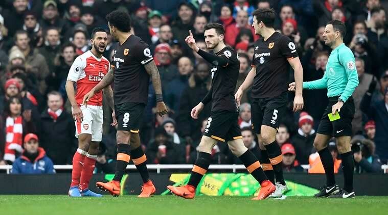 Arsenal's Theo Walcott clashes with Hull City's Harry Maguire, Andrew Robertson and Tom Huddlestone as referee Mark Clattenburg looks on