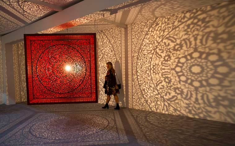 A woman walks near an art by Anila Quayyum Agha during India Art Fair in New Delhi, India, Thursday, Feb. 2, 2017. The four day art fair brings together a number of modern and contemporary artists to present their works. (AP Photo/Tsering Topgyal)