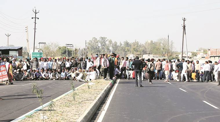 Security personnel keep vigil as Dera followers stage a protest on the Ludhiana-Malerkotla state highway Sunday. Gurmeet Singh
