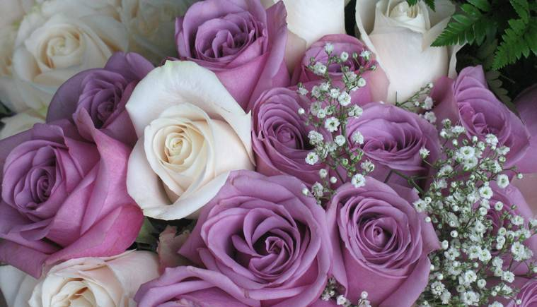 Purple and white roses with baby's breath makeup this beautiful bridal bouquet.