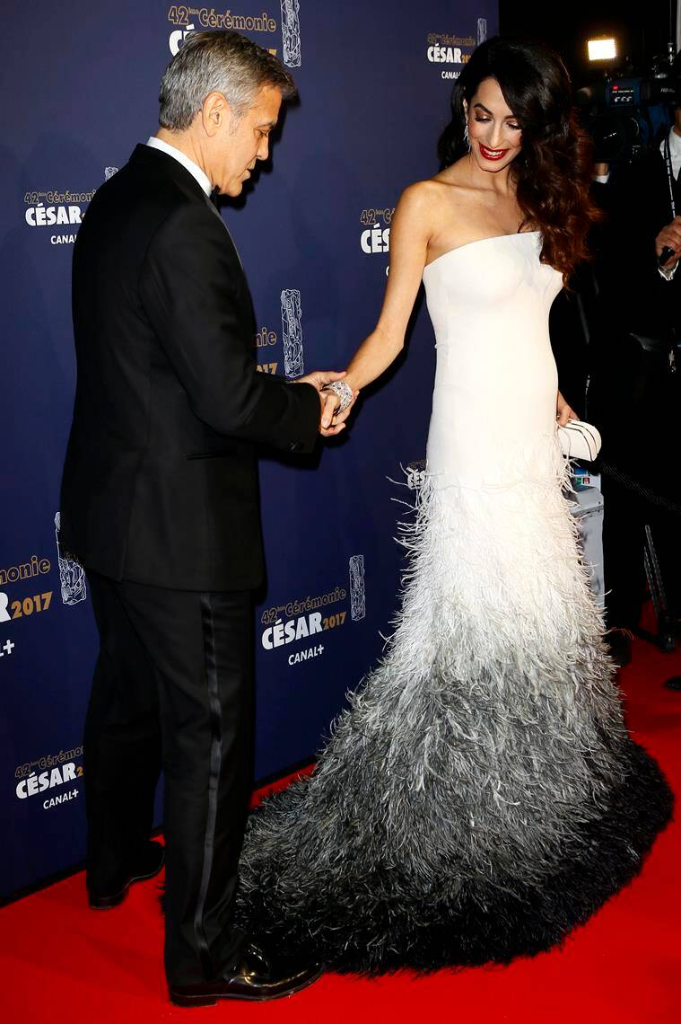 George Clooney holds Amal Clooney's hand at the 42nd Cesar Film Awards ceremony at Salle Pleyel in Paris. (Source: AP Photo)