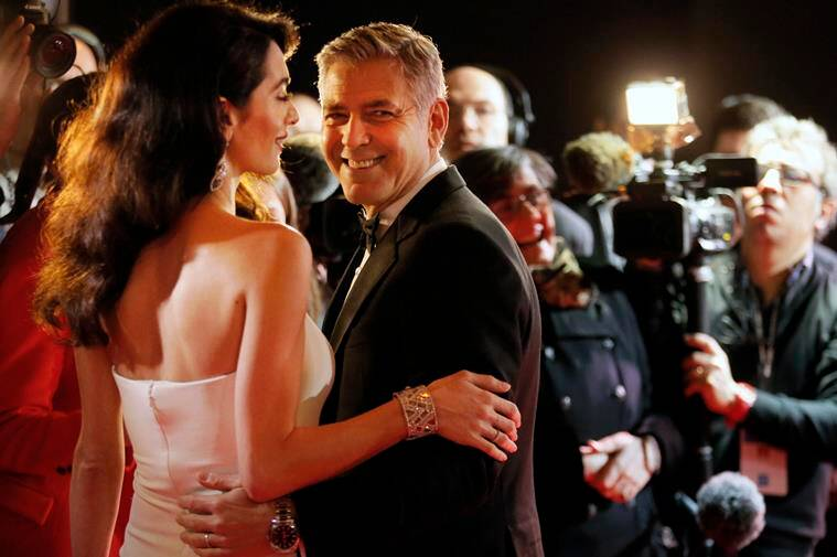 George Clooney and Amal Clooney held each other affectionately. (Source: AP Photo)