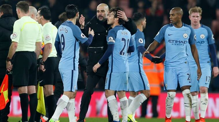 Manchester City manager Pep Guardiola celebrates with David Silva and Nolito after the game