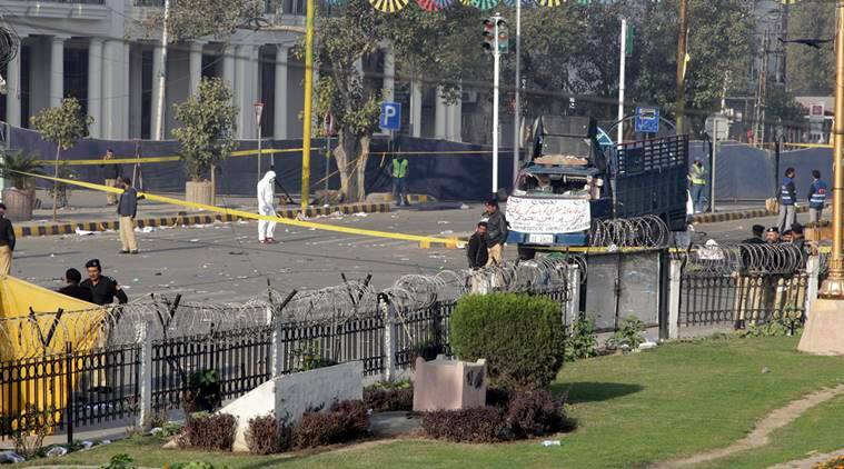 Pakistani investigators work at the site of a deadly bomb blast on Monday, in Lahore, Pakistan, Tuesday, Feb. 14, 2017. Markets and businesses were closed across much of Pakistan's Punjab province Tuesday in mourning for over a dozen people killed in the suicide bombing claimed by a breakaway Taliban faction. (AP Photo/K.M. Chaudary)