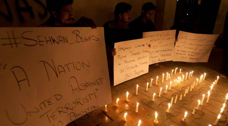 Pakistani students light candles to condemn the attack on a shrine in interior Sind province, Thursday, Feb. 16, 2017 in Karachi, Pakistan. An Islamic State suicide bomber targeted worshippers at a famous shrine in southern Pakistan on Thursday, killing dozens of worshippers and left hundreds of people wounded, officials said. (AP Photo/Shakil Adil)