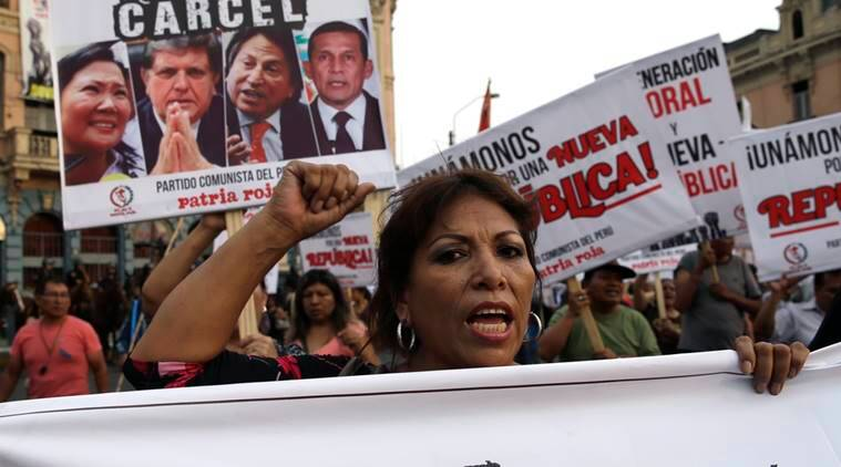 "A woman takes part in an anti-corruption march backdropped by a poster featuring images of three former Peruvian presidents, Alan Garcia, from left, Alejandro Toledo, and Ollanta Humala, with a message that reads in Spanish; ""To jail"", in Lima, Peru, Thursday, Feb. 16, 2017. Odebrecht, a Brazilian construction company, has admitted to paying almost 0 million in bribes to governments across Latin America as part of a December plea agreement with the U.S. Justice Department. In Peru, they acknowledged paying  million for projects built during the government of Toledo and two successors, Garcia and Humala. (AP Photo/Martin Mejia)"