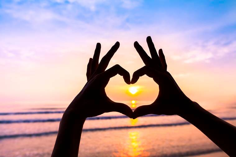 Woman's hands creating in the shape of heart with sunset background - symbol of love, romance, friendship, harmony