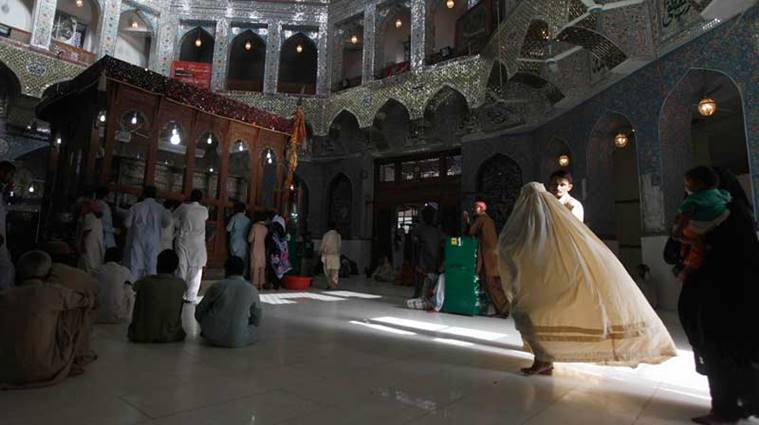 A woman clad in burqa walks in the hallway of the tomb of Sufi saint Syed Usman Marwandi, also known as Lal Shahbaz Qalandar, in Sehwan Sharif, in Pakistan's southern Sindh province, September 5, 2013.  Picture taken September 5, 2013. To match Feature PAKISTAN-SUFI/    REUTERS/Akhtar Soomro (PAKISTAN - Tags: SOCIETY RELIGION)