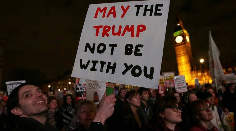 Demonstrators hold placards as they listen to speeches in London, Monday Feb. 20, 2017, during a rally in Parliament Square opposing U.S. President Donald Trump as Members of Parliament debate his planned state visit to the United Kingdom. (AP Photo/Tim Ireland)