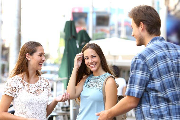 Candid girl with a friend flirting with a boy in the street