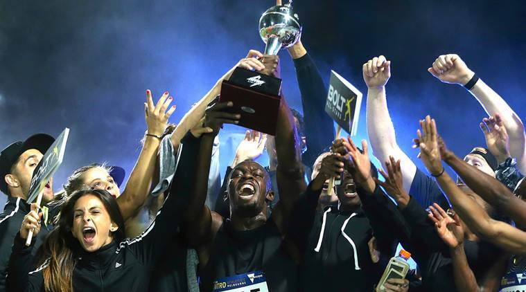 Jamaica's Olympic champion Usain Bolt holds the trophy aloft as he celebrates with team mates during the final night of the Nitro Athletics series at the Lakeside Stadium in Melbourne