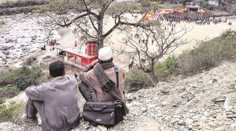 Two men watching a rally deep down in a valley in Pauri. (Source: Express photo by Ashutosh Bhardwaj)