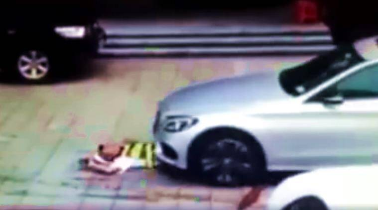 mercedes, car runs over security guard, security guard stops parking mercedes, car videos, china car runs over guard at parking lot, viral videos, indian express, indian express news