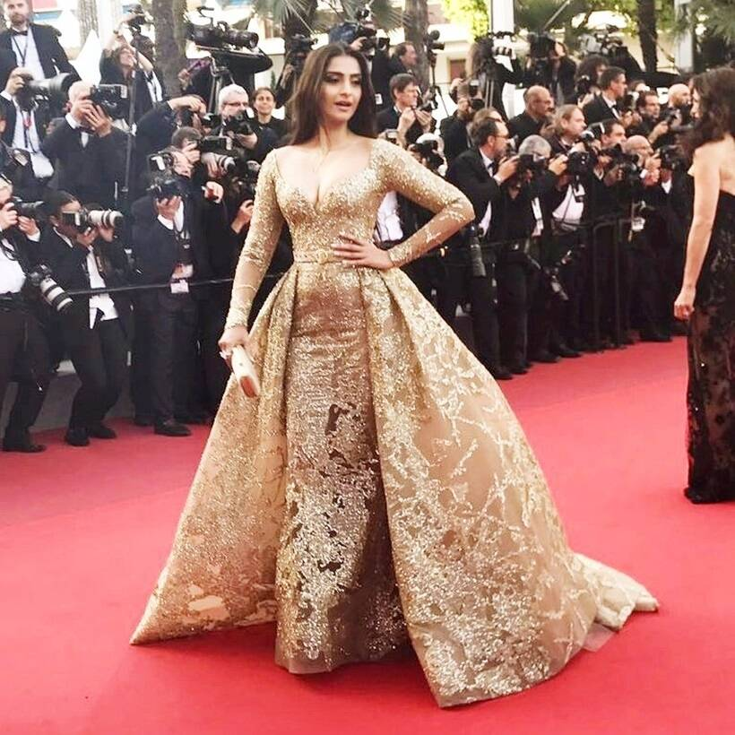 213ad9eaa92 Hit  Sonam Kapoor was seen in a shimmery body-fitting Elie Saab number with  a plunging neckline which was cinched at the waist with a sleek gold belt.