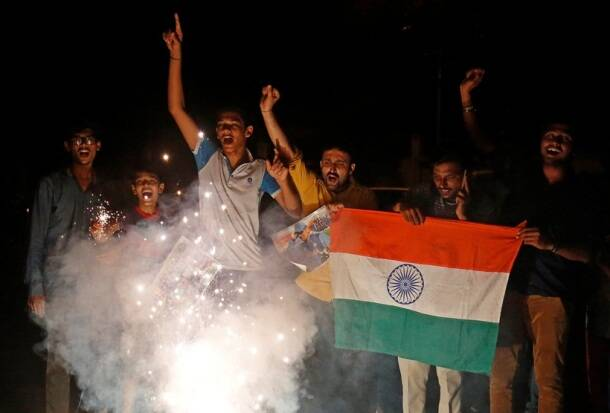 Fans light fireworks as they celebrate the victory of the Indian cricket team after the ICC Champions trophy match between India and Bangladesh in Birmingham, on a street in Ahmedabad