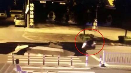 VIDEO: Busy talking on phone, man drives scooter right into a massivesinkhole